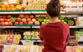 Pensive young woman looking at shelves with fresh fruits and vegetables at supermarket